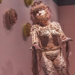 In a street-level window gallery space, which has a pale pink painted floor and walls, a life-size pink ceramic female figure stands on a low circular plinth that is covered in white and red fake fur. On the floor around the figure are several dark green and blue snakes. The body and head of the figure is covered in clay forms of flowers and leaves, the figure has long pink hair that almost reaches the floor. The hands are holding pink hair strands which have snake heads. On the wall behind the figure are several yellow ochre, orange and pink ceramic flower heads.]