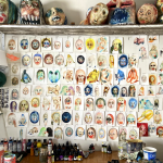 A wall in an artist studio is covered with a grid of small watercolour paintings of heads of creatures and monsters, above is a shelf with large masks of creatures. On the table there are paints and art supplies.